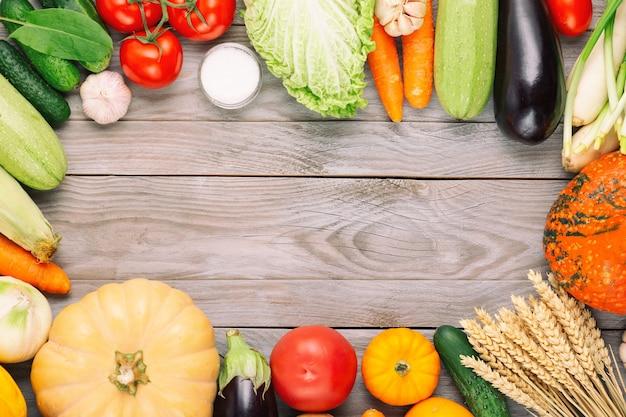 Frisches gemüse auf holztisch. frisches vegetarisches essen im garten. herbstsaisonbild des bauerntisches mit pilzen, roggen, gurken, tomaten, kohl, kürbissen, salz und auberginen.