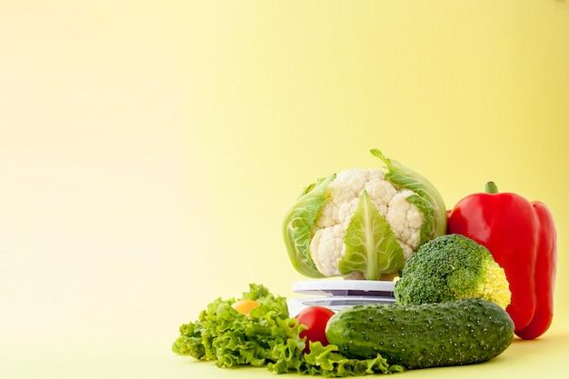 Frisches gemüse auf vase auf gelbem hintergrund. gesunde ernährung, diätplanung, gewichtsverlust, entgiftung, konzept des ökologischen landbaus