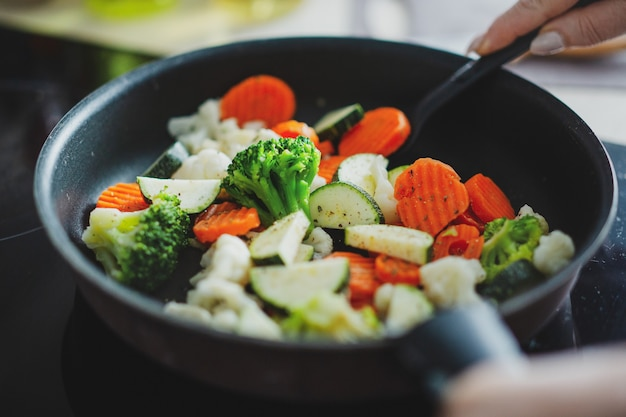 Frisches gemüse, das zu hause auf pfanne kocht. nahansicht.
