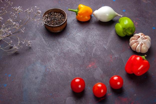 Frisches gemüse der halben draufsicht mit pfeffer auf gemüsemahlzeit-gewürzzutat des dunklen hintergrunds