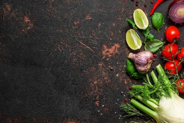 Frisches gemüse, gewürze und kräuter auf schwarzem steintisch