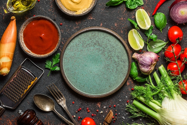 Frisches gemüse, gewürze und kräuter mit teller, besteck und utensilien auf schwarzem tisch