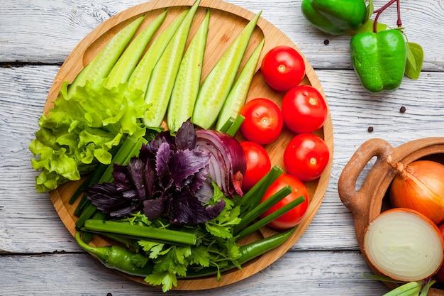Frisches gemüse gurke, tomate, zwiebel, pfeffer auf holzschneidebrett