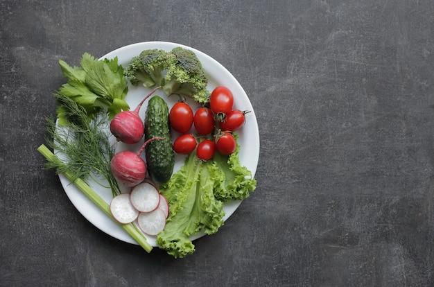 Frisches gemüse in einem weißen teller auf einem grauen tisch