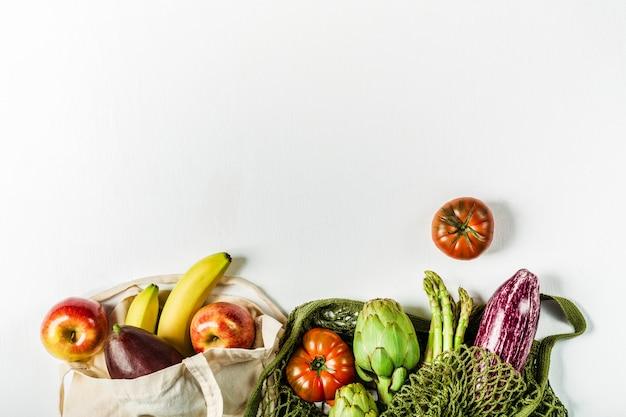 Frisches gemüse in einer grünen saitentasche und obst in einer tasche aus natürlichen materialien, umweltfreundlicher produkthintergrund
