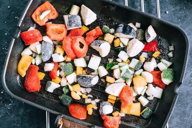 Frisches gemüse in einer schwarzen grillpfanne auf dem tisch mischen