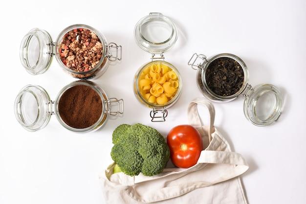 Frisches gemüse in einer umweltfreundlichen beigen einkaufstasche auf weißer wand. gläser mit grünem tee, müsli, kaffee, nudeln. kein abfallkonzept.