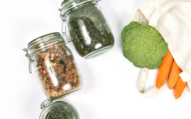 Frisches gemüse in einer umweltfreundlichen beigen einkaufstasche auf weißer wand. gläser mit grünem tee und müsli. kein abfallkonzept.