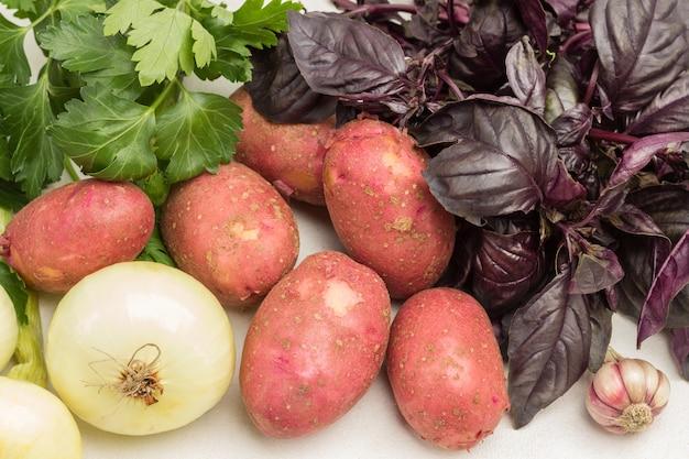 Frisches gemüse, kartoffeln und petersilie und basilikum. nahaufnahme. weißer hintergrund