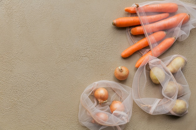 Frisches gemüse kartoffeln, zwiebeln, karotten in einem wiederverwendbaren netzbeutel mit kordelzug verpackt. ablehnung von plastikverpackung. umweltfreundliche verpackung.