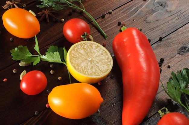 Frisches gemüse, kräuter und gewürze auf einem holztisch. zutaten für eine vegetarische mahlzeit. diät