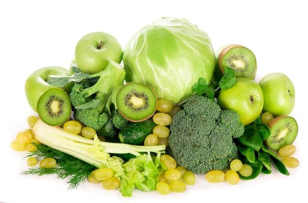 Frisches gemüse mit blättern - brokkoli, kiwi, sellerie, spinat, grünkohl, trauben und apfel lokalisiert auf weißem hintergrund