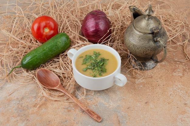 Frisches gemüse mit leckerer suppe auf marmor
