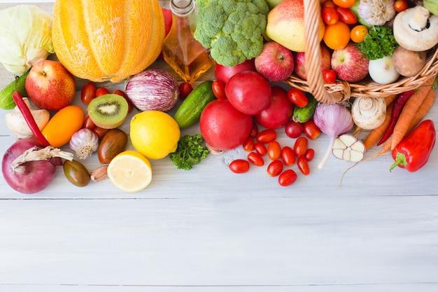 Frisches gemüse, obst und andere lebensmittel auf einer hölzernen tischoberansicht.