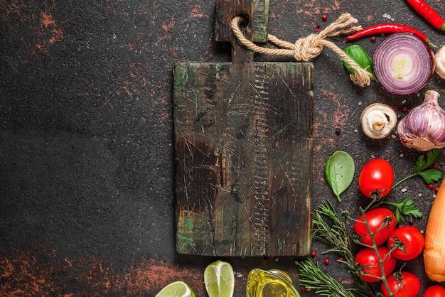 Frisches gemüse, pilze, gewürze und kräuter mit schneidebrett auf schwarzem steintisch