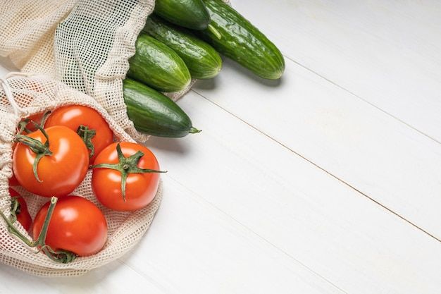 Frisches gemüse, tomaten und gurken in umweltfreundlichen beuteln