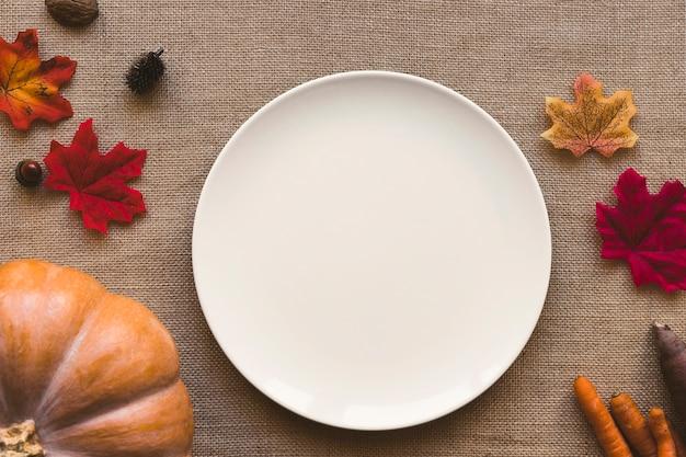 Frisches gemüse und blätter in der nähe von platte