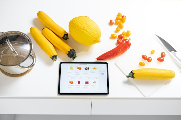 Frisches gemüse und digitaler tisch mit laufender eshop-website auf dem weißen tisch