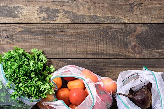 Frisches gemüse und gemüse in wiederverwendbaren umweltfreundlichen beuteln auf braunem holzhintergrund mit kopierraum