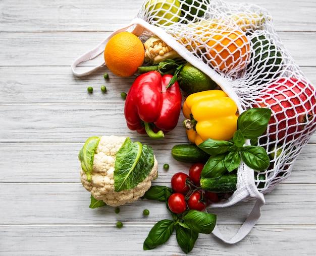 Frisches gemüse und obst auf öko-saitentasche auf einem weißen holztisch. gesunder lebensstil. draufsicht. kein verlust.