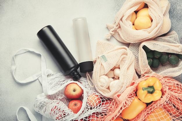 Frisches gemüse und obst in öko-taschen, wiederverwendbare wasserflaschen. zero waste einkaufen