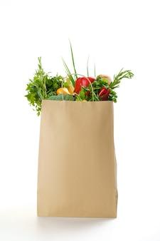 Frisches gemüse und obst in papiertüte, isoliert. bio-vegetarisches essen, lebensmittelprodukte, gesundes lebensstilkonzept