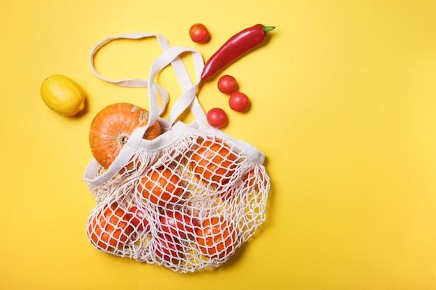 Frisches gemüse und obst in wiederverwendbarer saitentasche aus ökologischer baumwolle