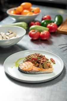 Frisches gemüse und schüssel mit gehackten champignons, teller mit gebratenem gemüse auf gebratenem lachs auf küchentisch