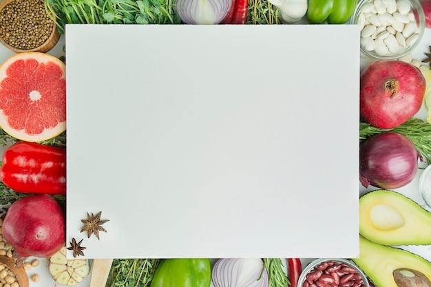 Frisches gemüse und zutaten für gesundes kochen. diät- oder vegetarisches lebensmittelkonzept. kochhintergrund, kräuter, salz, gewürze, olivenöl, weißer hintergrund. speicherplatz kopieren. tabellenhintergrundmenü.