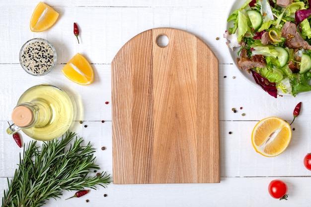 Frisches gemüse und zutaten zum kochen auf weißem hölzernem hintergrund. modell mit leerem holzschneidebrett. vegetarisches und gesundes ernährungskonzept.