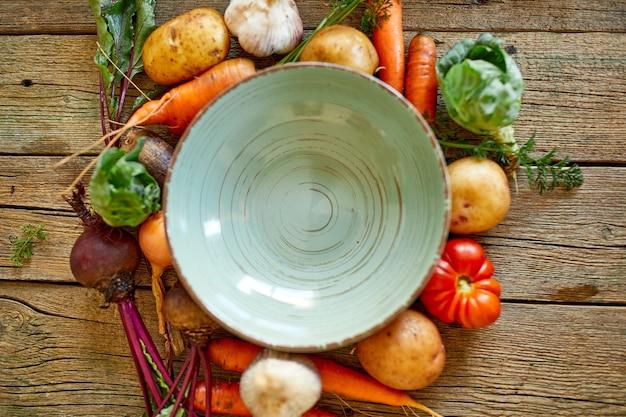 Frisches gemüse zum kochen von suppe um einen runden grünen leeren teller auf einem hölzernen hintergrund eines tisches von oben, gesundes lebensstil- und lebensmittelkonzept, vegetarisches, biologisches essen.