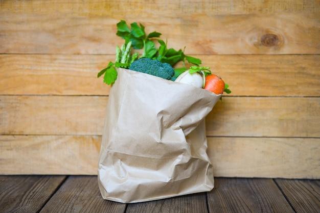 Frisches gemüse zum mitnehmen papiertüten einkaufen, lieferung gesunder lebensmittel und papiertüte einkaufen