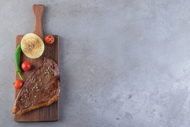 Frisches geschnittenes fleisch mit frischem gemüse, das auf einen steinhintergrund gelegt wird.