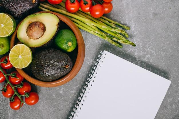 Frisches gesundes gemüse der draufsicht in der hölzernen platte und im leeren notizbuch auf grau