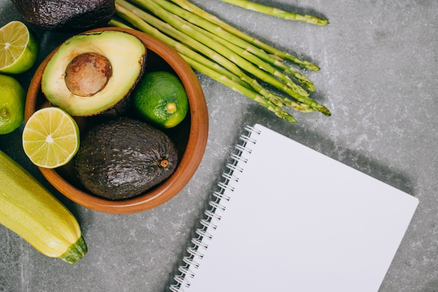Frisches gesundes gemüse des draufsichtgrüns in der hölzernen platte und im leeren notizbuch auf grau