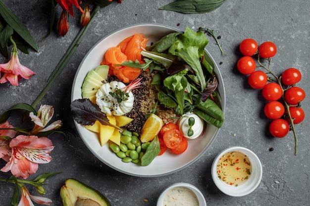 Frisches gesundes leichtes frühstück, geschäftsessen. frühstück mit pochiertem ei, buchweizen, rotem fisch, frischem salat, gurken und kirschtomaten, geschäftsessenkonzept.