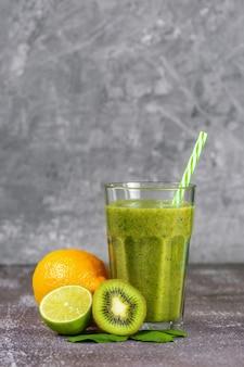 Frisches gesundes smoothiegetränk in einem hohen glasglas mit einem strohhalm, umgeben von früchten. das konzept der richtigen ernährung, gewichtsverlust, entgiftung des körpers.