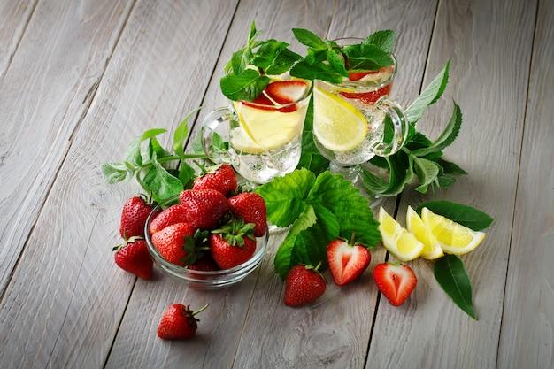 Frisches gesundes sommergetränk mit zitrone und erdbeeren mit eis.