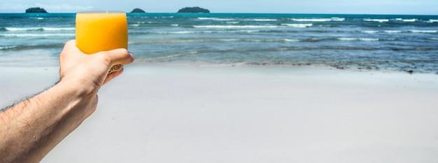 Frisches getränk in der hand des mannes auf dem hintergrund des exotischen strandes, nahaufnahme
