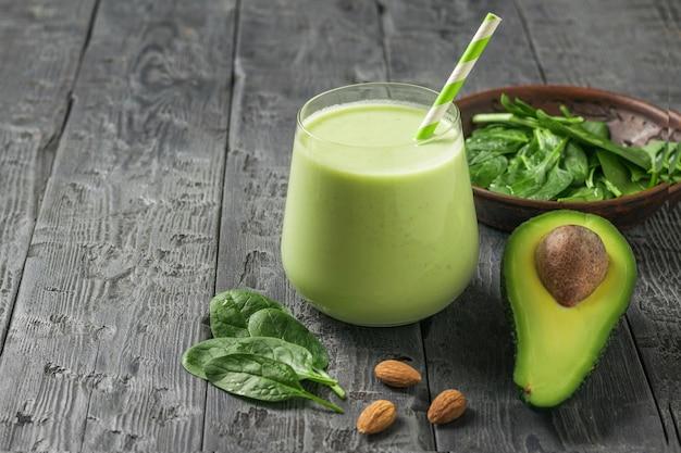 Frisches getränk, spinatblätter und eine halbe avocado auf einem rustikalen tisch. fitnessprodukt. diätetische sporternährung.