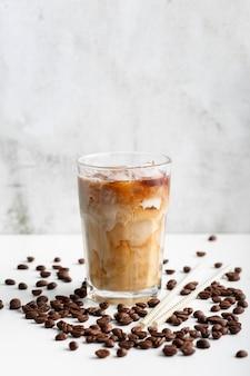 Frisches glas kaffee mit milch auf dem tisch