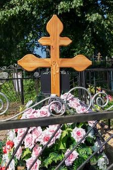 Frisches grab mit einem kreuz auf dem friedhof. trauer und erinnerung. vertikal.