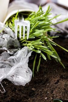 Frisches gras wächst im boden und müll aus menschlichem abfall.