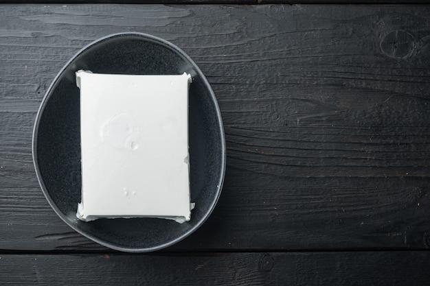 Frisches griechisches feta-käse-set, auf schwarzem holz, flach gelegt