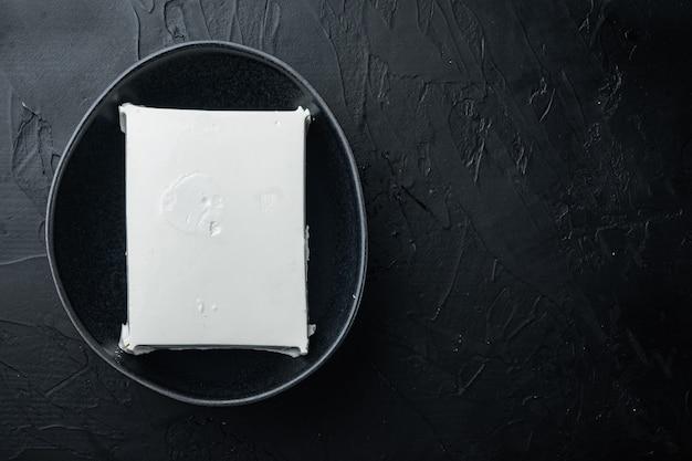 Frisches griechisches feta-käse-set, auf schwarzem tisch, flach gelegt