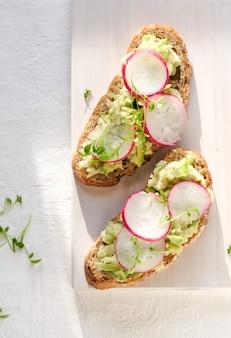 Frisches grünes frühlingssandwich mit avocado und rettich