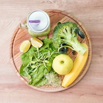 Frisches grünes gemüse und grüner smoothie im glas