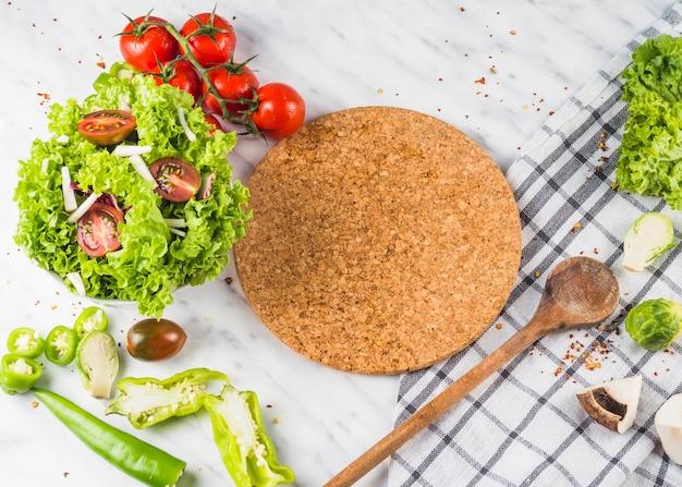 Frisches grünes gemüse und hölzerner costar des gesunden bauernhofes auf die küchenoberseite