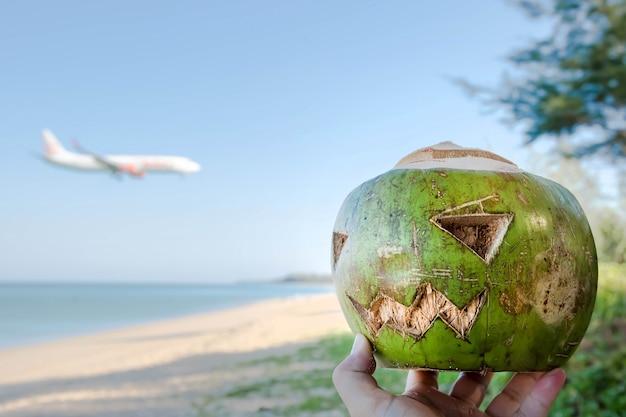 Frisches grünes kokosnusssymbol von halloween mit geschnitztem gesicht auf kürbis liegt auf gras am sandstrand