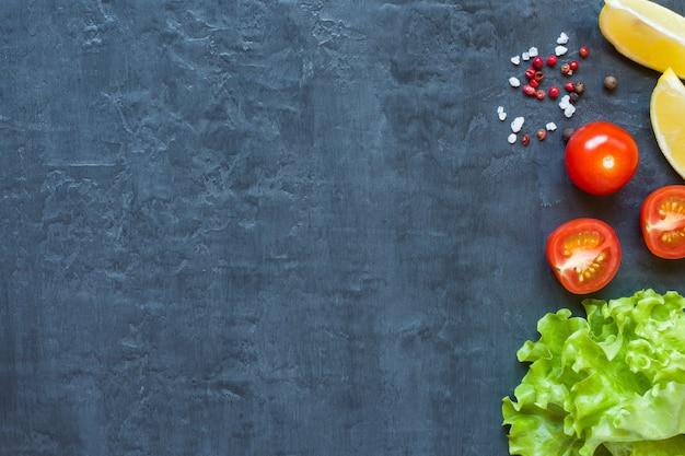 Frisches grünes kopfsalatblatt, kirschtomaten, zitrone und gewürze auf dunklem hintergrund